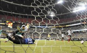 El jugador de la selección de México Raúl Jiménez marca un gol al guardameta de Trinidad y Tobago Jan Michael Williams (i) durante el partido por los